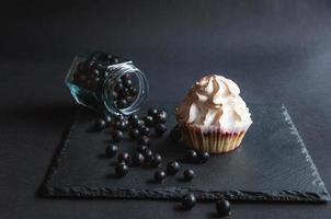 Muffin with currants on a black background and scattered berries. photo