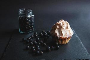 Appetizing baked vanilla muffin with currants on a black board. photo