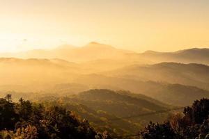 hermosa capa de montaña con nubes y amanecer foto