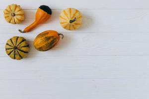 Pumpkins on white wooden background top view. Autumn composition. photo