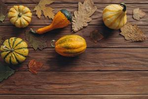 Pumpkins, dried leaves on white wooden background top view. Autumn. photo