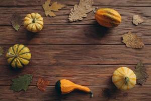 Produce pumpkins, autumn leaves on wood table photo