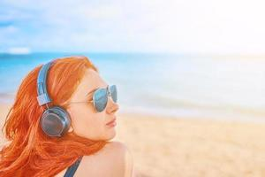 Beautiful woman in sunglasses listening to music on the beach photo
