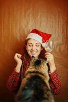 Hembra pelirroja con sombrero de santa claus y gato esponjoso foto