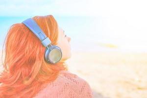 Beautiful woman listening to music on the beach photo