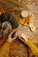 Women's hands with ball of yarn, coffee and cane photo