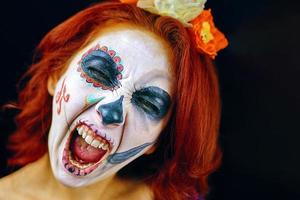 A young woman in day of the dead mask skull face art photo