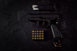 Flat lay of cartridges and gun on concrete background photo