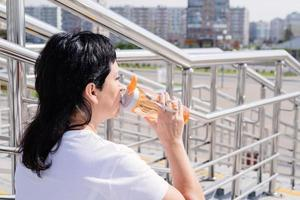 Senior woman drinking water after workout outdoors on urban background photo