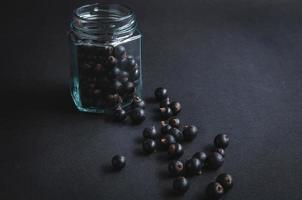 Fresh blueberries in a glass jar on a black board. photo