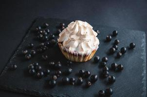 Muffin on a black background with currant berries. photo