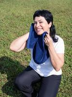 Senior woman wiping out sweat after hard workout outdoors in the park photo