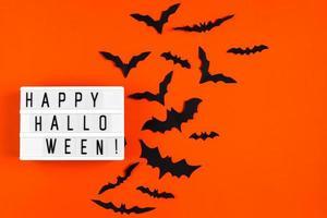 Halloween concept. Festive decorations. Bats on orange background. photo