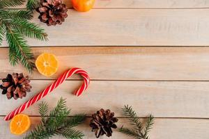 New Year. Christmas tree branches, pine cones, tangerines and candies photo