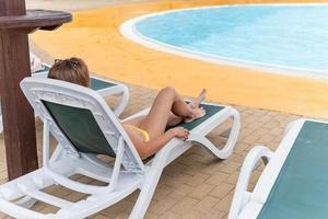 The beautiful young woman lying on the sun lounger next to the pool photo