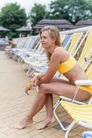 The beautiful young woman sitting on the sun lounger next to the pool photo