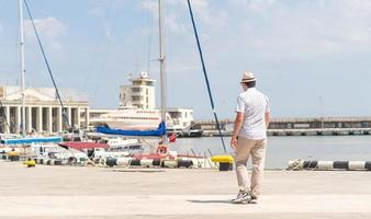 Tourist walking in the sea port, boats and yachts on the background photo