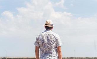 Back view of a man in shirt and summer hat looking at the sky photo