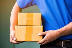 Close up Delivery man in blue uniforms holding parcel cardboard box. photo