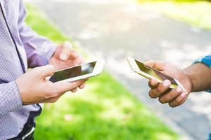 dos empresario con smartphone en el parque. foto