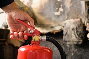 Close up hand Fireman using fire extinguisher fighting. photo