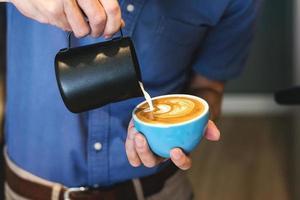 Barista making coffee latte art in a coffee shop photo