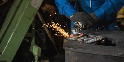 Industrial worker cutting metal and steel with many sparks photo