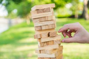 Close up hand man playing block wood stack game photo