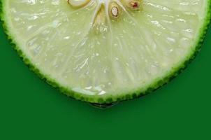 rodaja de limón y lima y cítricos frescos sobre fondo verde. foto