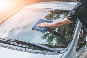 man cleaning car with microfiber cloth photo