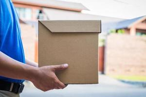 Close up hand holding parcel cardboard box, photo