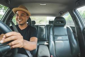 joven apuesto hombre asiático conduciendo un coche foto