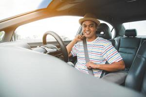 Young asian man putting on his seat belt in his car. photo