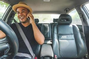 joven asiático con smartphone mientras conduce el coche foto