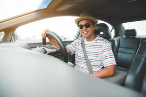 Young handsome asian man driving car to travel. photo