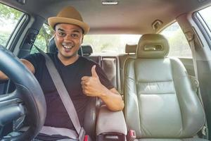 Young asian man showing thumb up while driving car. photo