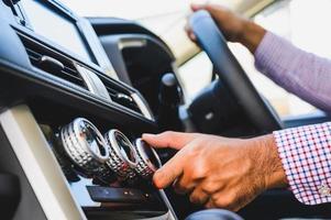Cerrar la mano masculina comprobando el aire acondicionado en el coche. foto