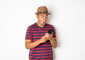 Hombre sorprendido usando el teléfono sobre fondo blanco. foto