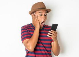 Shocked man using phone on white background photo