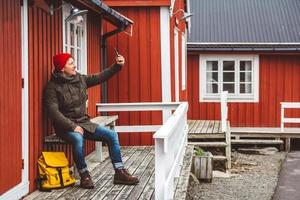 man sits near wooden red colored house taking self-portrait a photo