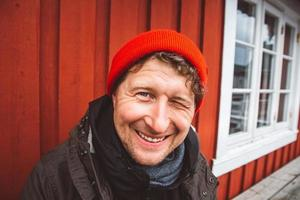 Portrait traveler man sits near the wooden red colored house photo
