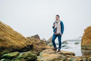 Hombre con una mochila de pie sobre una roca frente a un hermoso mar foto