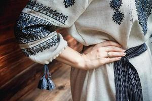 Details of bride's embroidered shirt on background of a wooden house photo