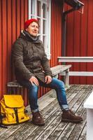 Traveler man sits near wooden red colored house photo