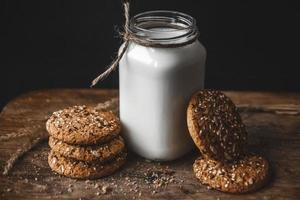 Cereal cookies with a jug of milk on a wooden background. photo