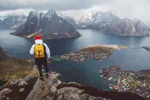 man with a backpack standing on background of mountains and sea photo