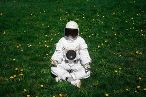 Futuristic astronaut in a helmet sits on a green lawn among flowers photo