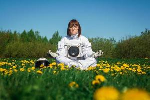 woman astronaut without a helmet sits on a green lawn among flowers photo
