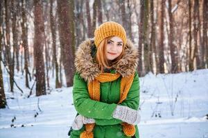 woman in winter clothes on a background of snow-covered forest photo