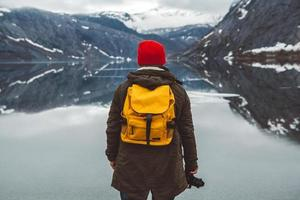 man standing on background of mountains and lake makes a photo